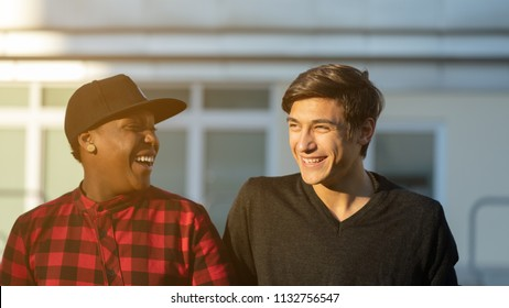 black friend and white friend outdoors in an informal portrait chatting each other