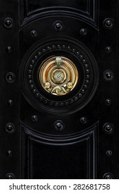 Black front door with brassy ornate snake, London, UK