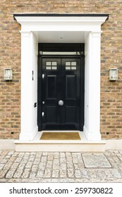 Black front door of a house with glass windows, London UK