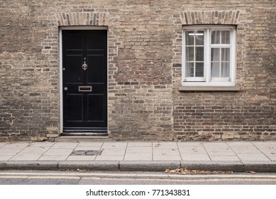 Black front door on a restored brick wall of a Victorian house residential building with white wooden sash window