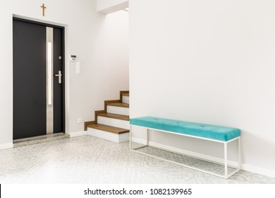 Black front door, stairs and a turquoise upholstered bench seat in a white entrance hall interior