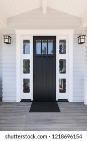 Black front door with white trim and multiple windows