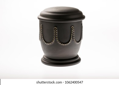 black funeral urn with golden decoration on bright background for condolence card