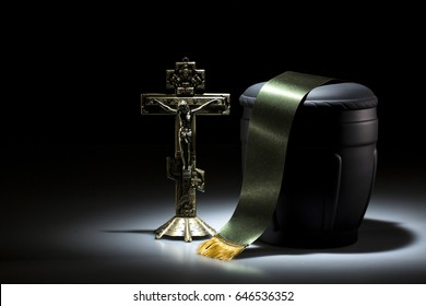 black funerary urn with orthodox cross on dark background