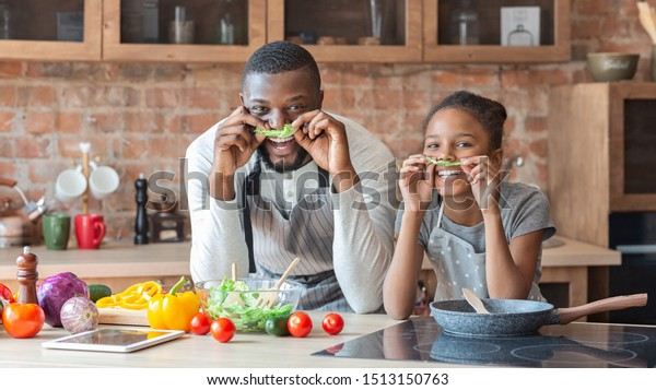 Black funny father and daughter making mustaches with lettuce, having fun while cooking at kitchen, panorama with empty space