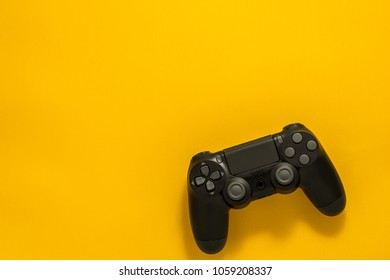 black gamepad on a yellow background. Gaming concept. Flat lay copyspace.