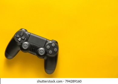 black gamepad on a yellow background. Gaming concept
