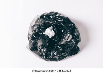 Black garbage bag with thrown napkin on white background top view