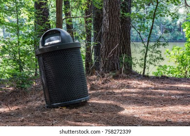 Black garbage can in the woods with a lake in the background.