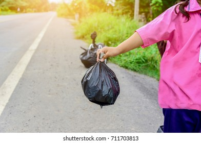 Black garbage in the children hand stand on road on green background