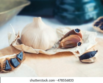 Black Garlic background in a soft focus showing Black garlic glove cut in half on a wooden board . room at base for copy space and text.