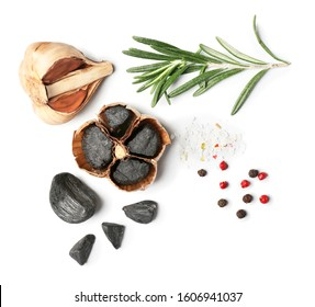 Black garlic, herbs and spices on white background