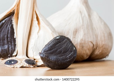 Black garlic - made from fresh garlic and fermented. It is odorless and very healthy Asian food ingredient. Close up shot with cloves and whole garlic.