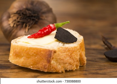 Black garlic on bread on an old wooden table