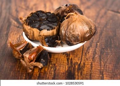 Black garlic on wooden background
