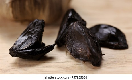 """Black garlic is a type of """"caramelized"""" garlic first used as a food ingredient in Asian cuisine. Black garlics on wooden chop. Selective focus."""