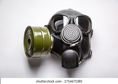 black gas mask with a filter lies on a table close-up on a white background. Horizontal orientation.