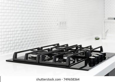 Black gas stove at brand new modern white kitchen