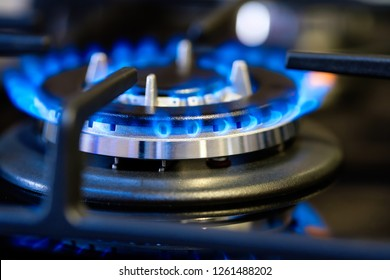 Black gas stove with burning blue flame