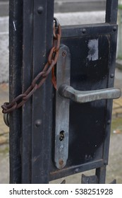black gate door lock with rusty chain on it