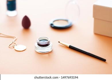 Black Gel eyeliner close up with a make up brush on the beige background