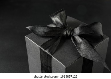 Black gift box with bow on black background, close up