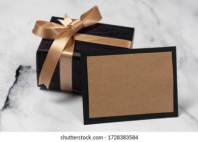 Black gift box with a golden ribbon With an empty Card on a white and black marble table.