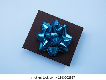 Black gift box on a blue contrasted background, decorated with a blue bow, creating a romantic atmosphere. Typically used for birthday, anniversary presents, gift cards, post cards.
