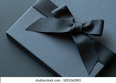 Black gift box on a dark contrasted background, decorated with a textured bow and feathers, creating a romantic atmosphere. Typically used for birthday, anniversary presents, gift cards, post cards.