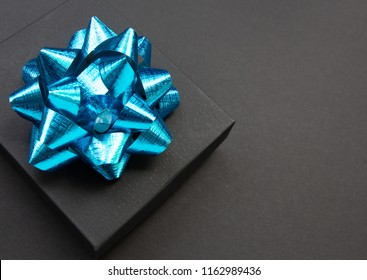 Black gift box on a dark contrasted background, decorated with a blue big bow, creating a romantic atmosphere. Typically used for birthday, anniversary presents, gift cards, post cards, letters.