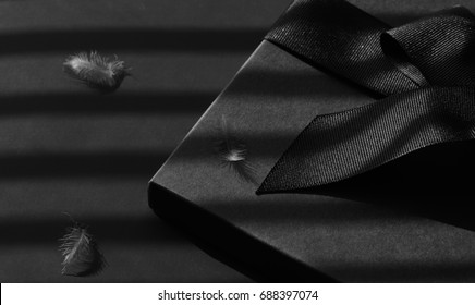 Black gift box on a dark contrasted background, decorated with a textured bow and feathers, creating a romantic atmosphere. Typically used for birthday, anniversary presents, gift cards,letters.