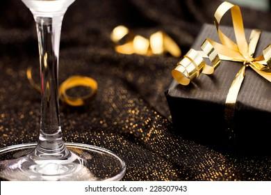Black gift box on black shiny background. Celebration