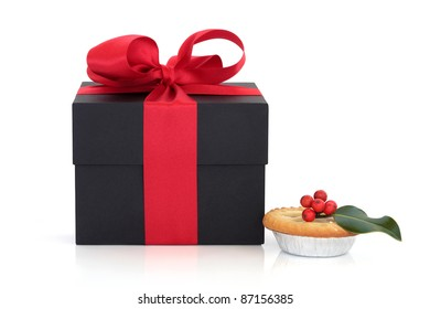 Black gift box with red satin ribbon and bow and christmas mince pie with holly berry leaf sprig isolated over white background.