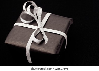 Black gift box with silver bow on black shiny background.