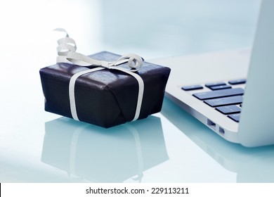 Black gift box with silver bow on light background next to the computer. On line shopping