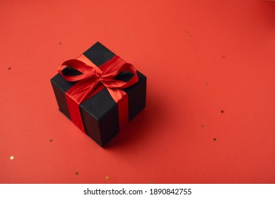 Black gift boxes with red ribbon on red background. The Concept Of Valentine's Day.
