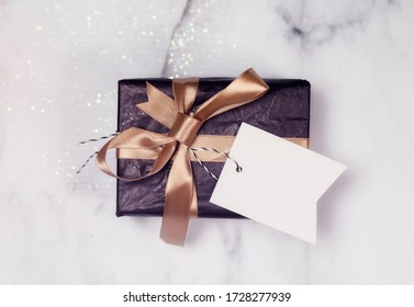 Black Gift With Gold Bow And Empty white Card on a white and black marble table with a bit of glitter.