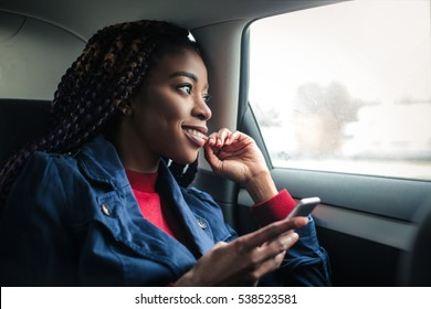 Black girl in a car feeling happy with her phone in her hands
