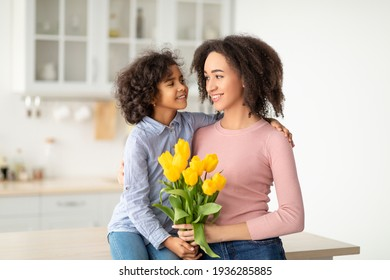 Black girl celebrating mother's day, greeting mum with tulips