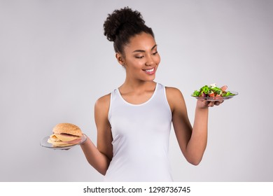 Black girl holding cheeseburger and salad isolated on white background.