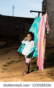 Black girl infront of a washing line with a huge smile on her face