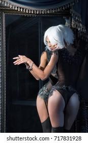 Black girl in black lingerie near the mirror