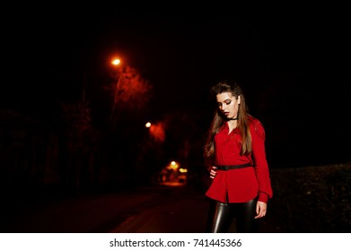 Black girl in red shirt and bright make-up on night street outdoor. Halloween theme.