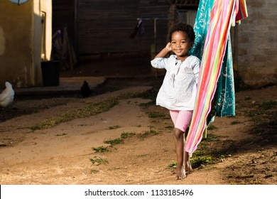 Black girl standing at the  washing line with her hand in her hair.