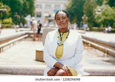 Black girl in a summer park. Lady with stethoscope. Woman in a yellow dress. Famale in a white overall