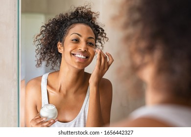Black girl take care of her beautiful skin. Young african woman applying moisturizer on her face. Smiling black natural girl holding little jar of skin lotion in bathroom for beauty treatment routine.