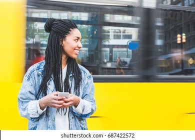 Black girl typing on smart phone in Berlin. Beautiful young woman in the city with a blurred tram in Alexanderplatz on background. Lifestyle, technology and travel concepts