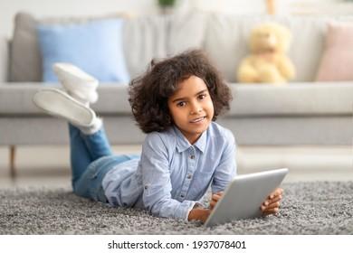 Black girl using digital tablet, lying on the floor