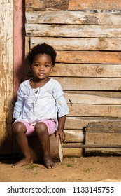 Black girl without shoes and a serious expression on her face