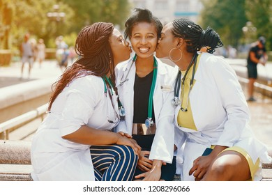 Black girls in a summer park. Ladies with stethoscope. Friends in a sunny sity. Women in a white overalls. Famale with stethoscope